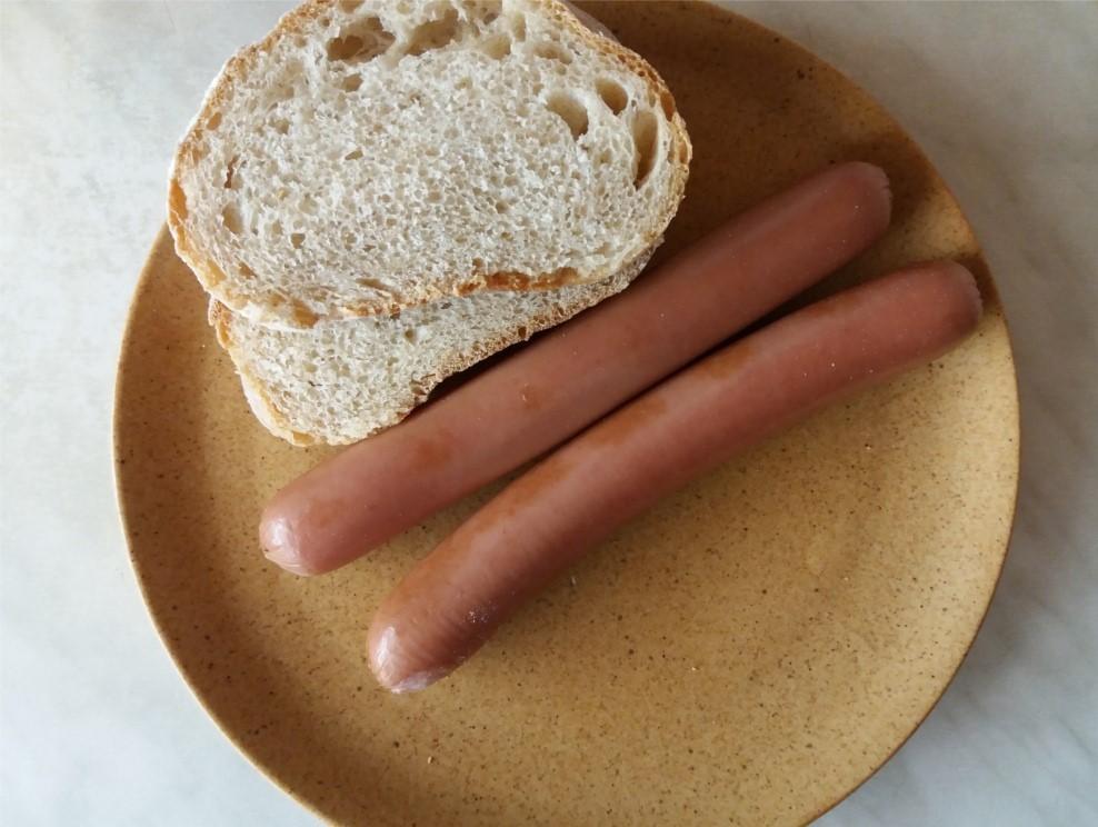 Főtt virsli házi kenyérrel tálalva